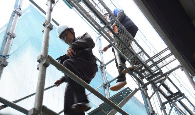 現場をまわり安全指導のため足場に登る